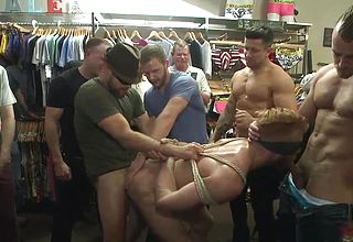 Gang fucked by muscular guys in a clothes store
